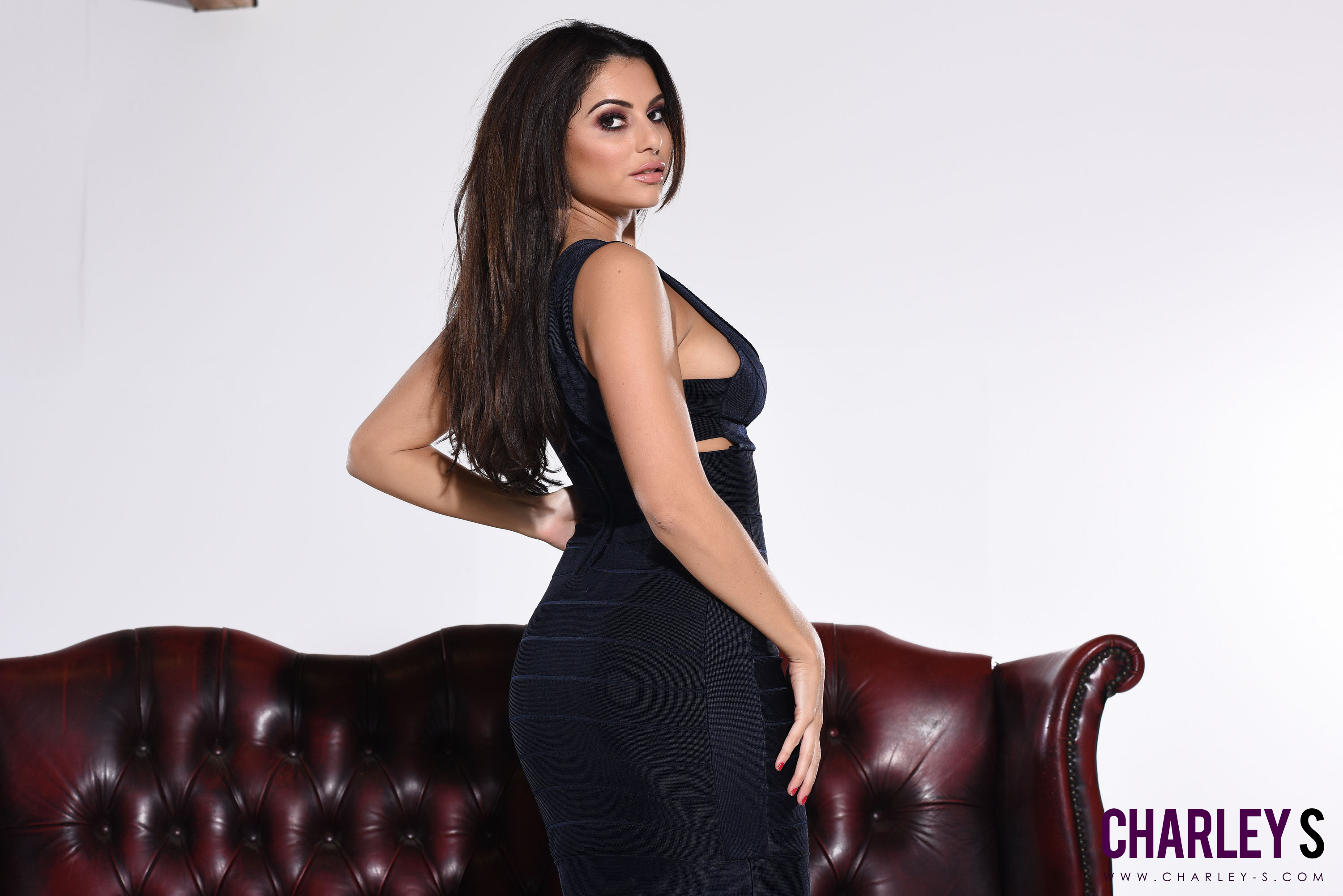 Essex tease posing on a chesterfield couch