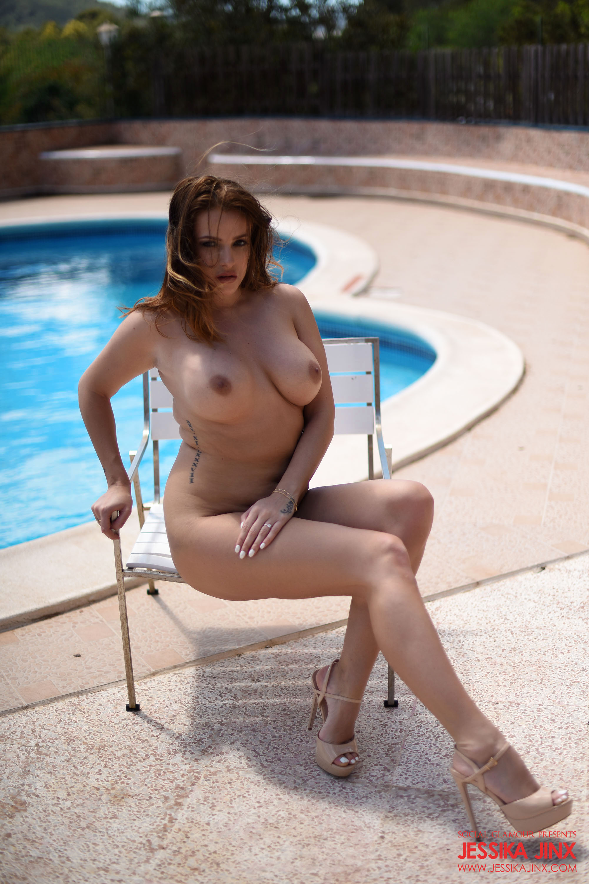 Curvy babe gets naked by the pool