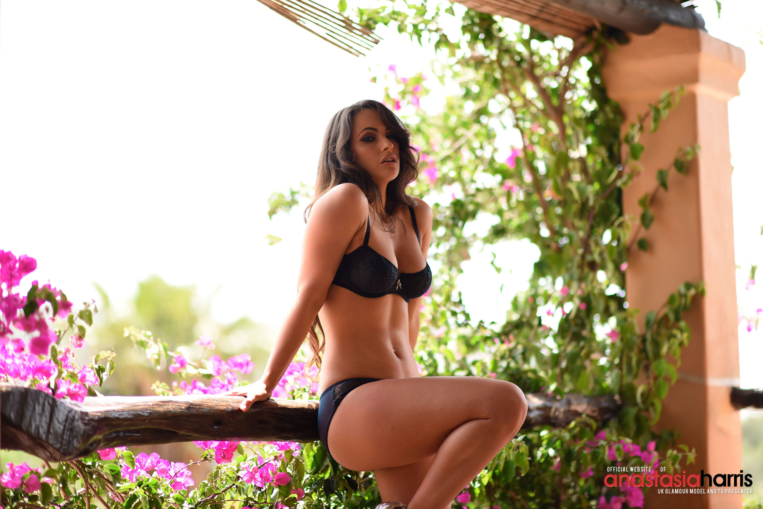 Anastasia posing in blue lingerie and heels outdoors