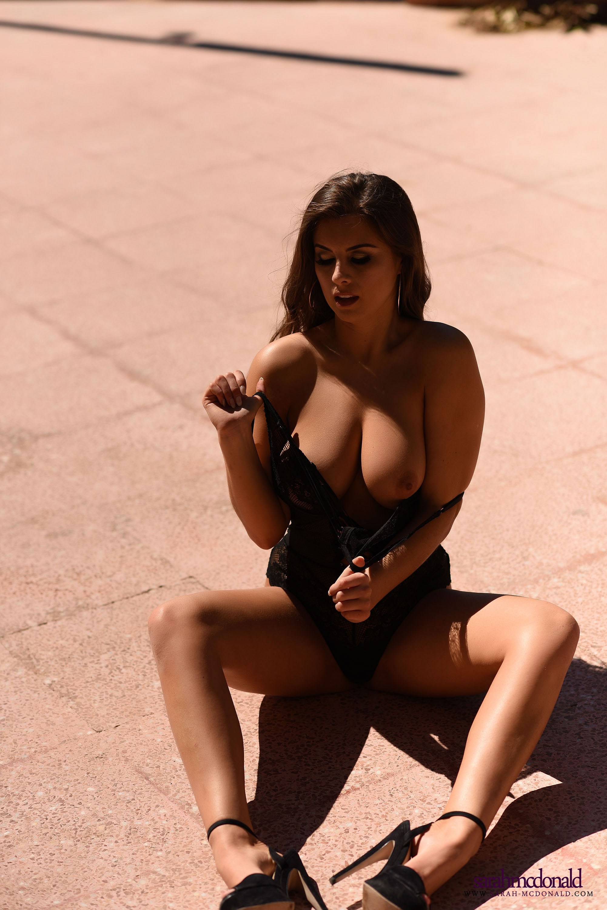 Gorgeous brunette lying topless outdoors